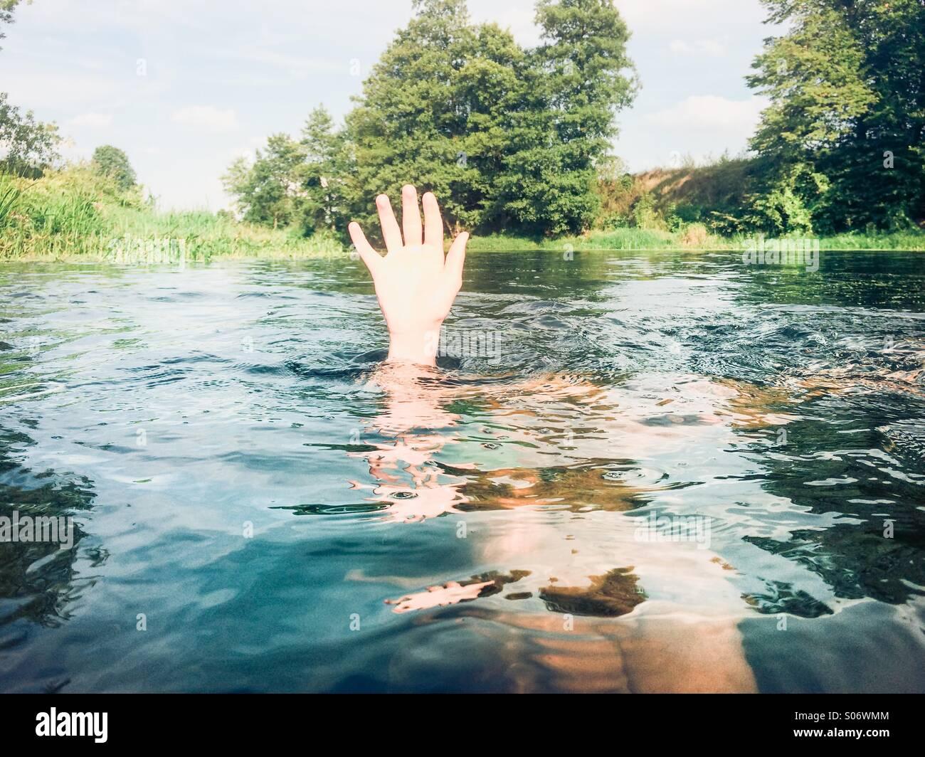 Junge in einem reinen Fluss hält seine Hand über dem Wasser untergetaucht Stockfoto