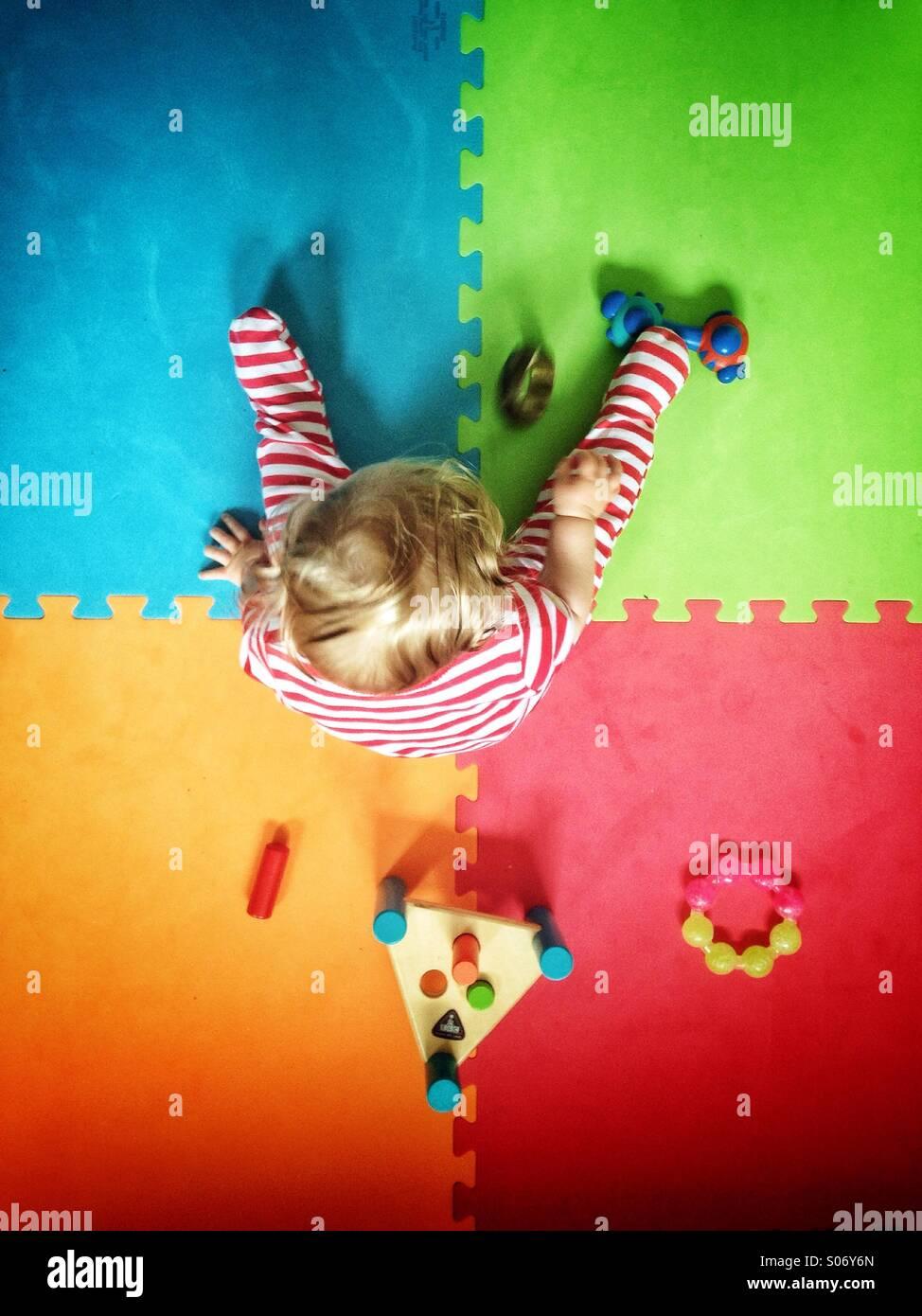 Baby spielt auf farbenfrohe Spielmatte Stockfoto