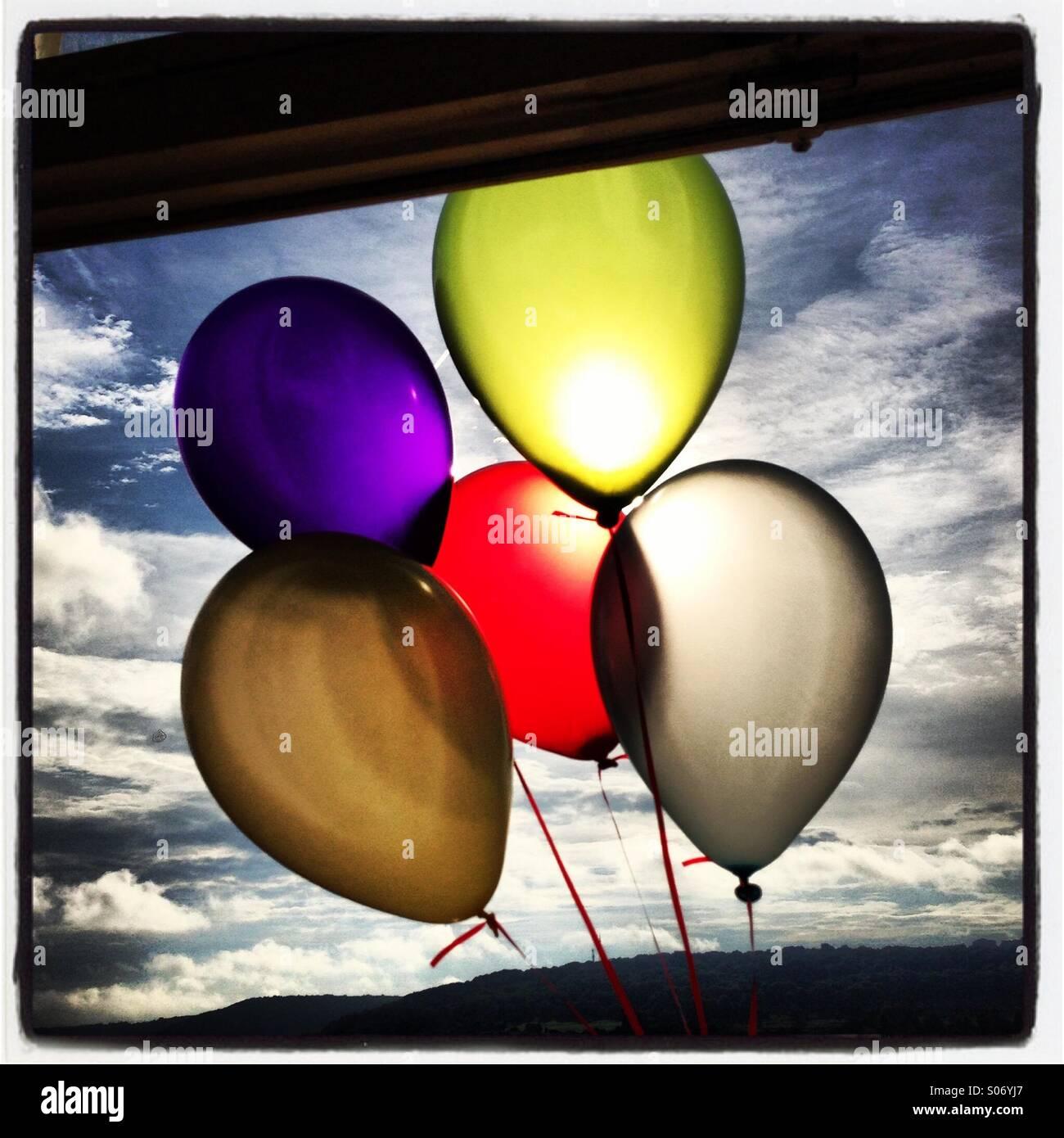 Bunten Ballons vor der Sonne vor einem Fenster vor blauem Himmel mit weißen flauschigen Wolken. Stockbild