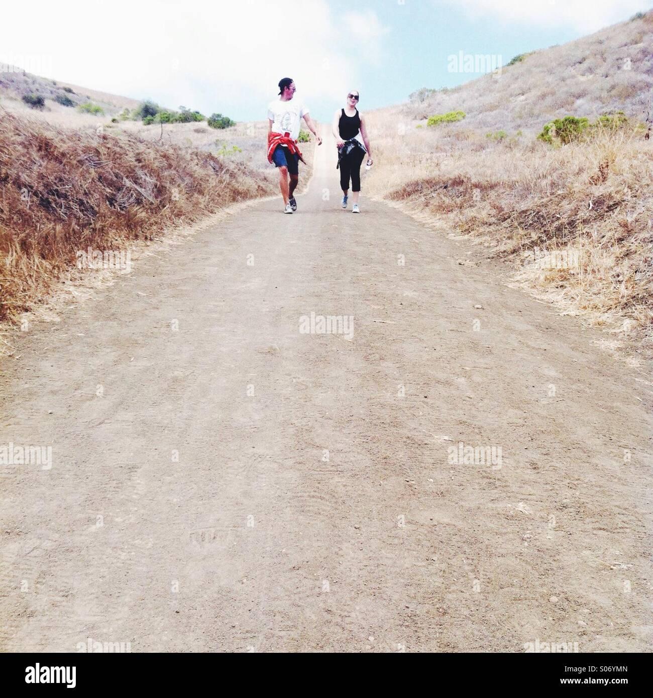 Jungen und Mädchen zu Fuß entlang der Strecke Stockbild