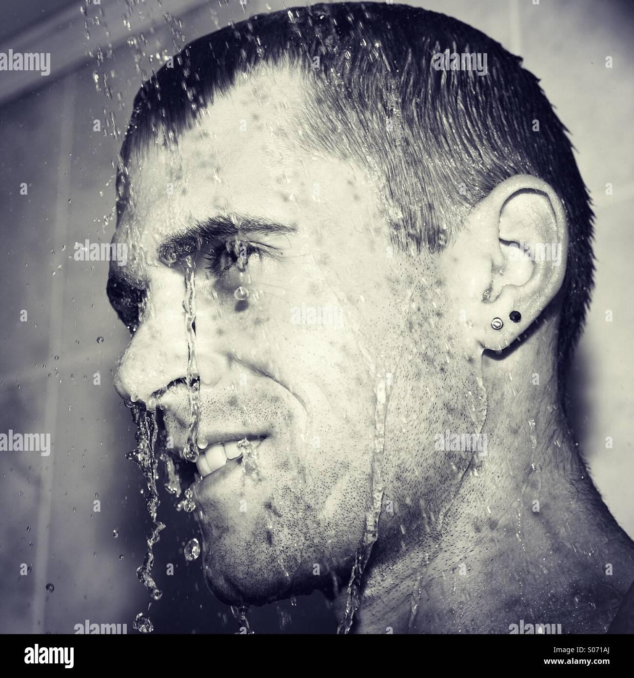 Glücklicher Kerl in der Dusche abkühlen Stockbild