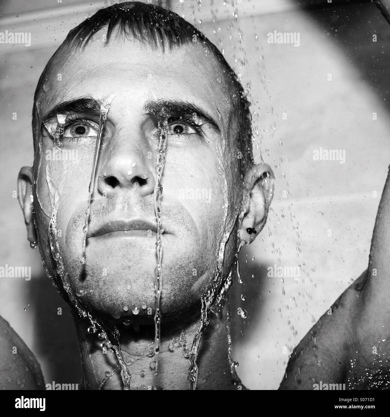 Kerl in der Dusche mit nassen Gesicht Stockbild