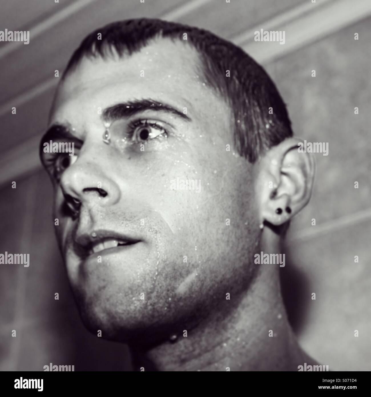 Mann mit nassem Gesicht in Dusche Stockbild