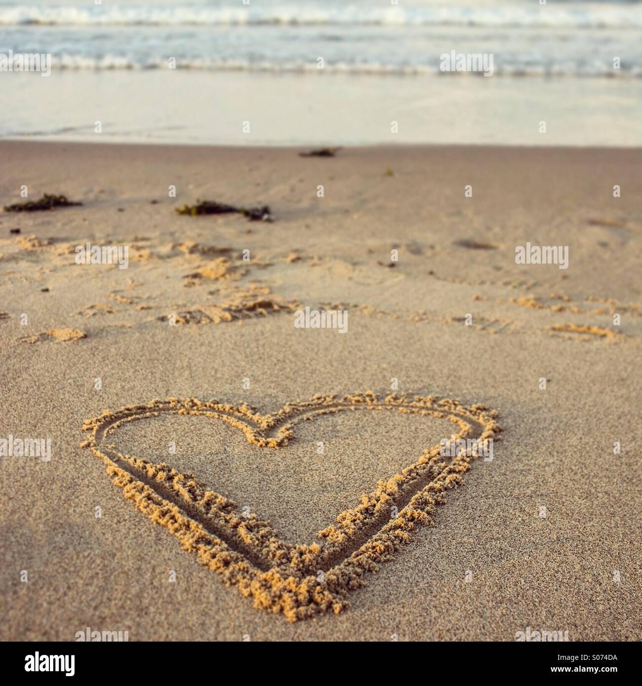 Herzform gezeichnet im Sand am Strand Stockbild