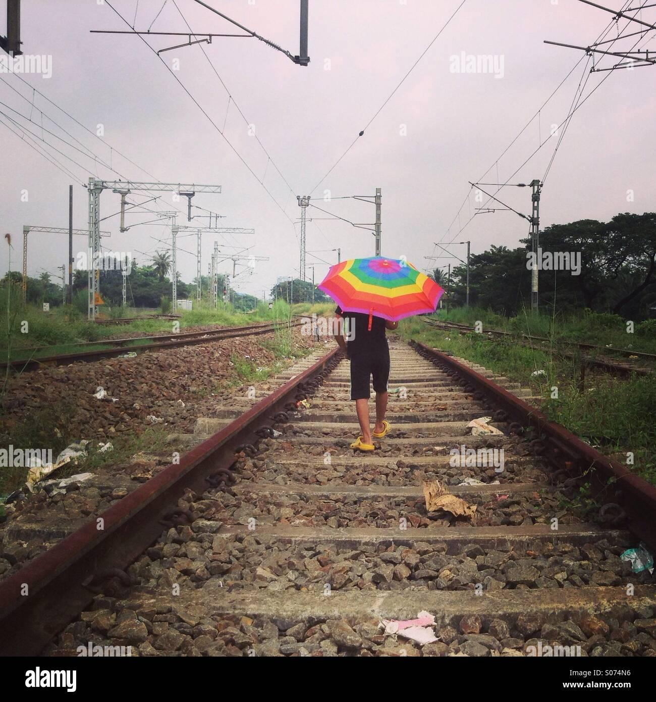 Jungen zu Fuß allein durch eine Eisenbahnstrecke Stockbild