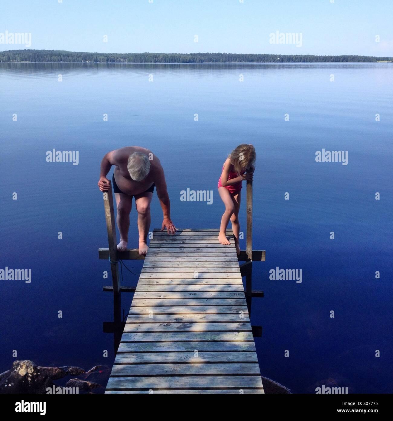Großvater und Enkelin gehen in einem nordischen See zusammen schwimmen Stockfoto