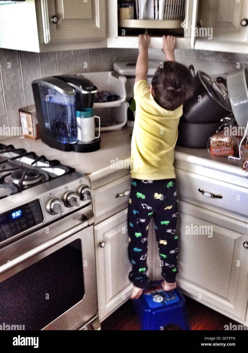 Ich kann es! Kleiner Junge stehend auf einem Hocker dehnen und in einer offenen Tür Schränke zu erreichen. Stockbild