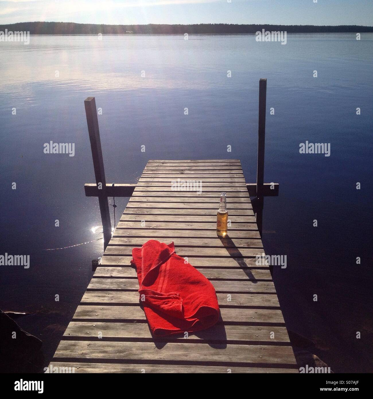 Ein kühles Bier und ein Handtuch auf einem Steg an einem idyllischen nordischen Sommerhaus See im Norden Finnlands Stockbild