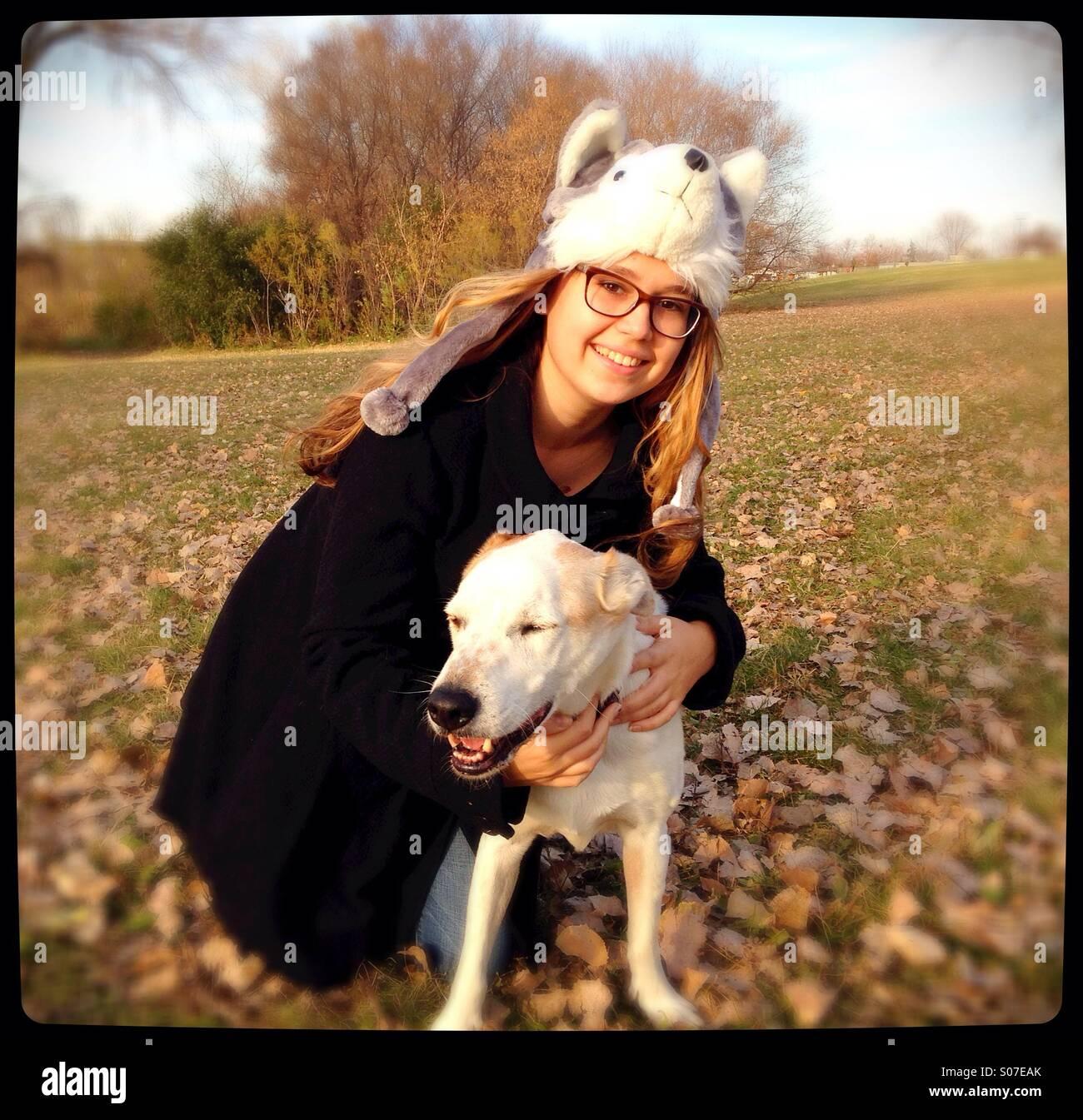 Ein junges Mädchen umarmt einen glücklichen Hund. Stockbild