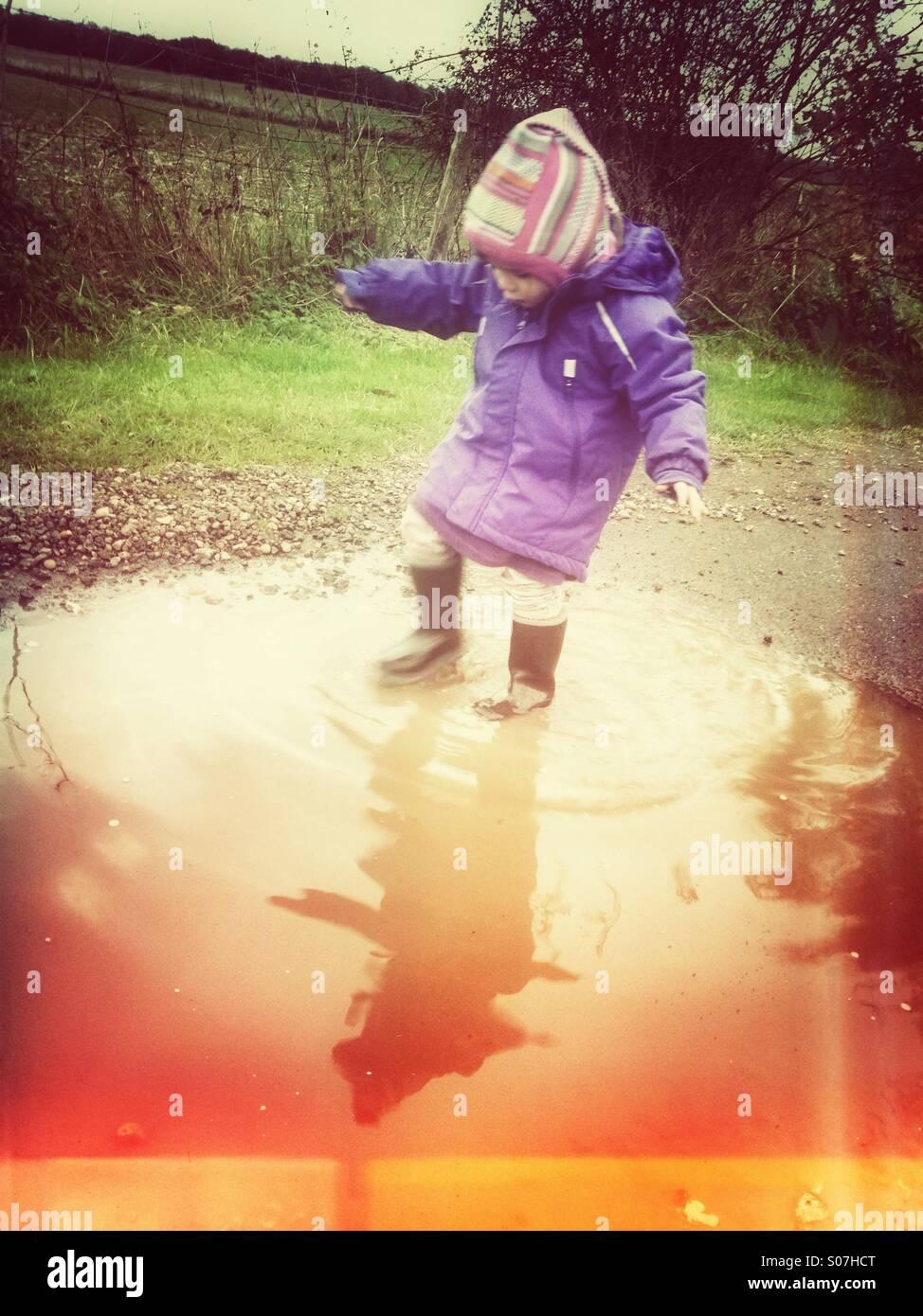 Kind im Alter von 2-3 Jahren spielen in Pfütze Stockbild