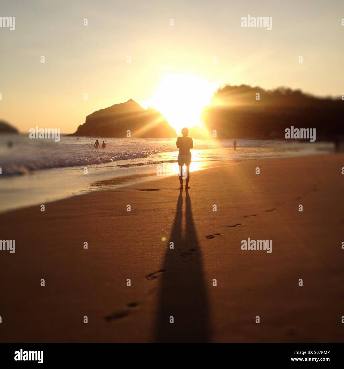 Frau am Strand bei Sonnenuntergang, Zipolite, Oaxaca, Mexiko Stockbild