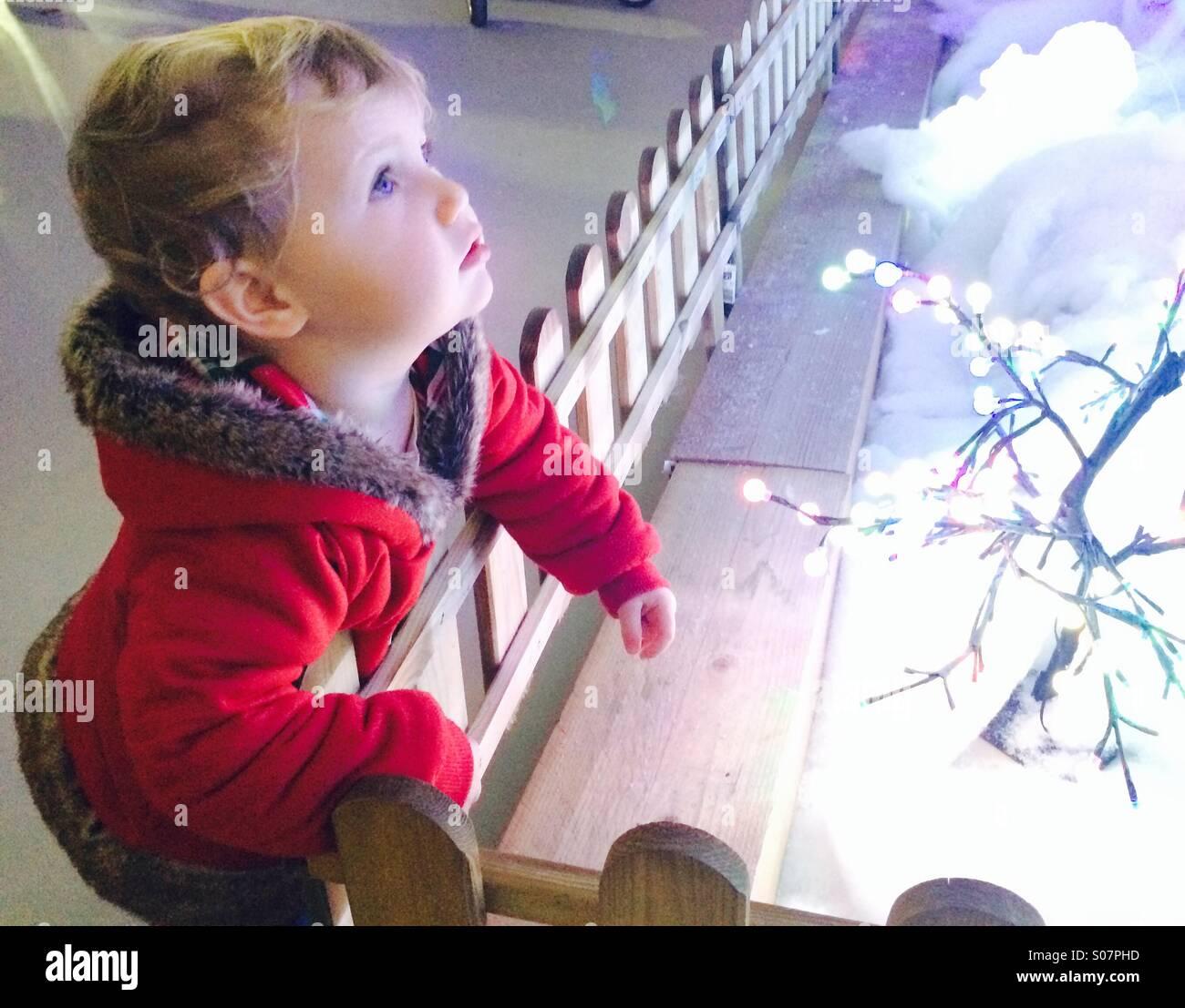 Kleines Mädchen starrte auf Weihnachtsbeleuchtung in Frage Stockbild