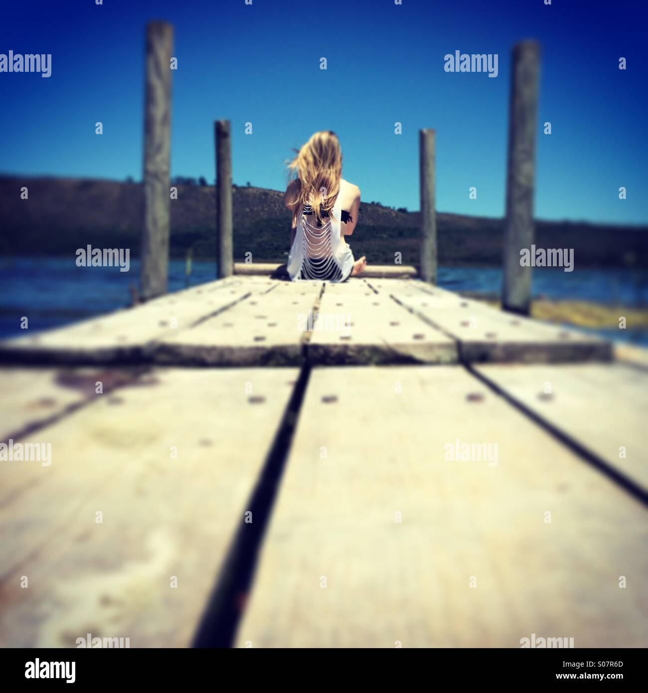 Junges Mädchen sitzt auf einem Steg Stockbild
