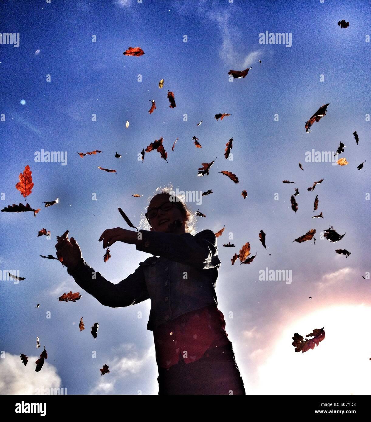 Junges Mädchen mit Herbstblätter fallen um sie herum Stockbild