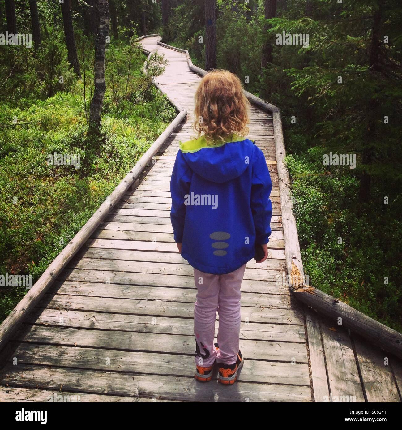 Ein junges Mädchen auf der Suche auf einen Weg durch einen dichten Wald in Nordfinnland in einem riesigen Nationalpark. Stockbild