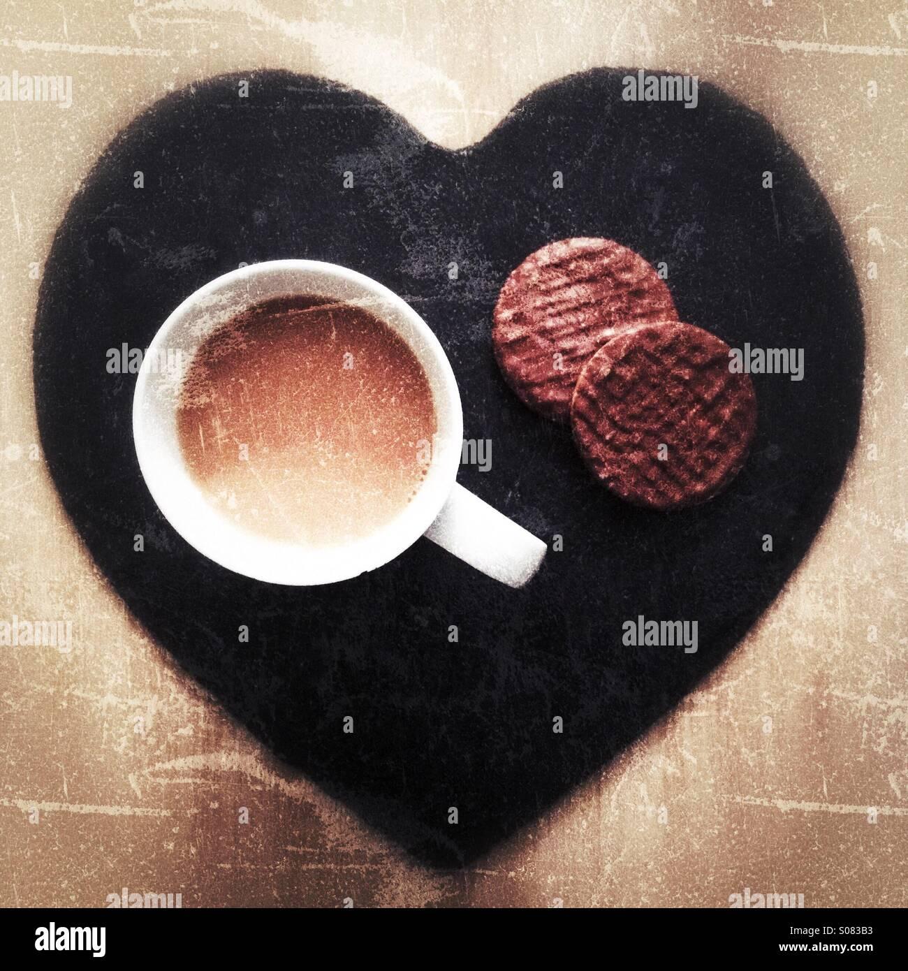 Eine Tasse Tee Witz zwei Schokoladenkekse sitzt auf einer Schiefertafel Herz. Stockbild
