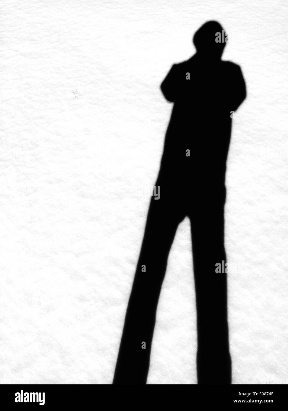 Schatten eines Mannes gegen den weißen Schnee. Stockbild