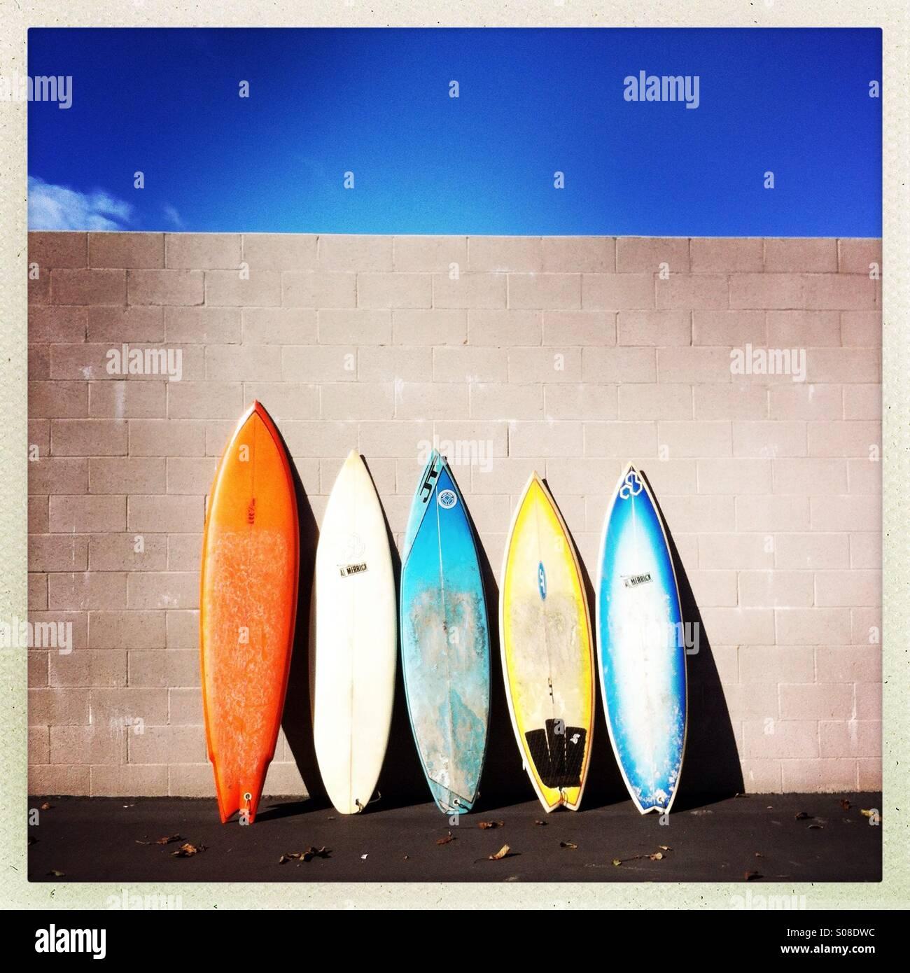 Bunte Surfbretter an eine Wand gelehnt. Stockbild