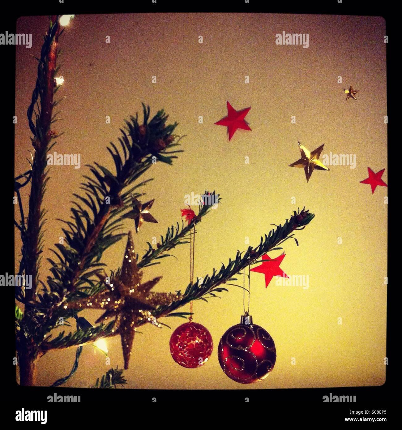 Detail von einem Weihnachtsbaum dekoriert mit Kugeln und Lichterketten, mit roten und goldenen Sternen im Hintergrund Stockbild