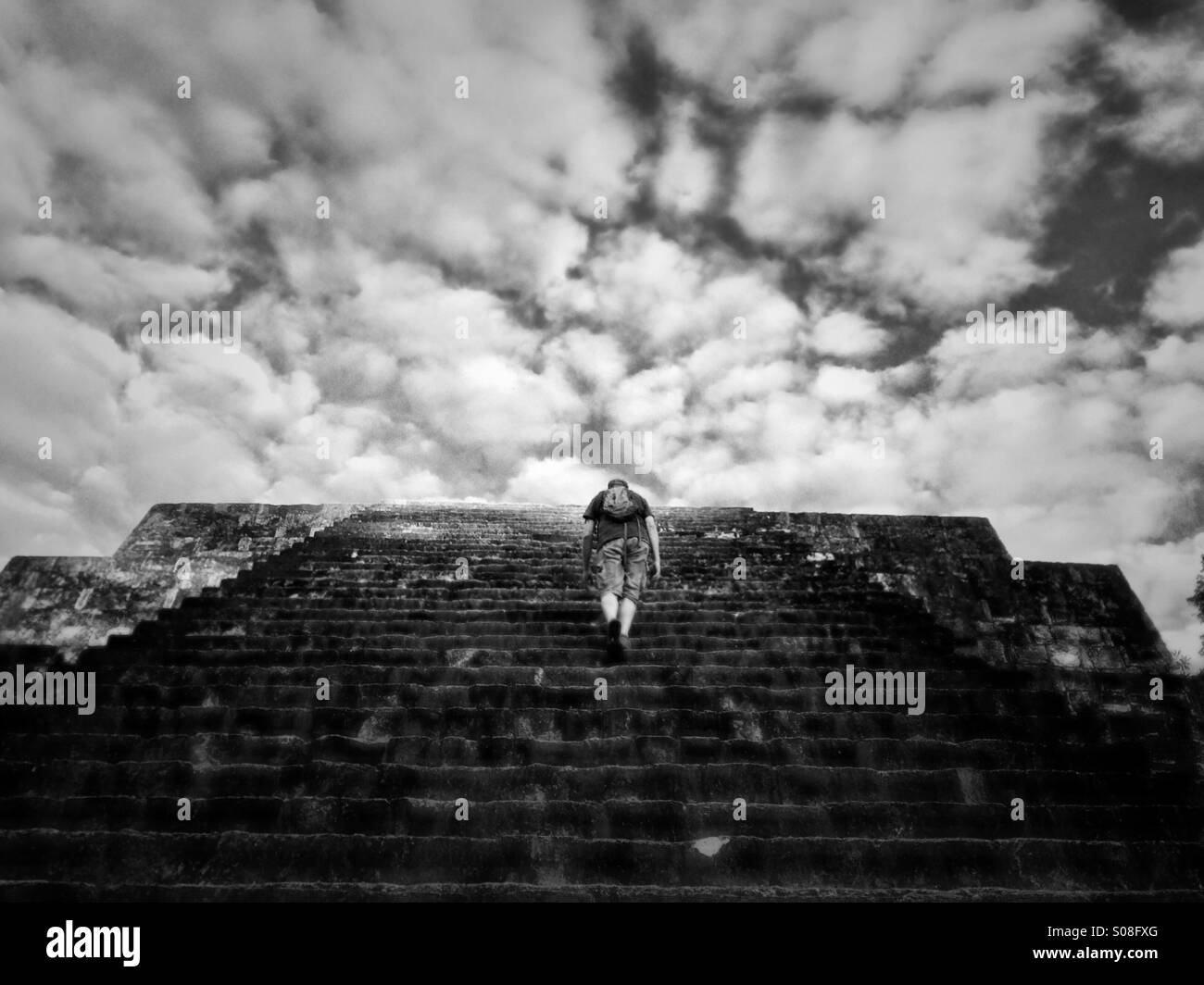 Mann Klettern Pyramide von Tikal, Guatemala Stockbild