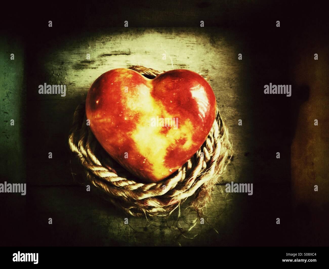 Rote Glas-Herz mit einem Seil Stockbild