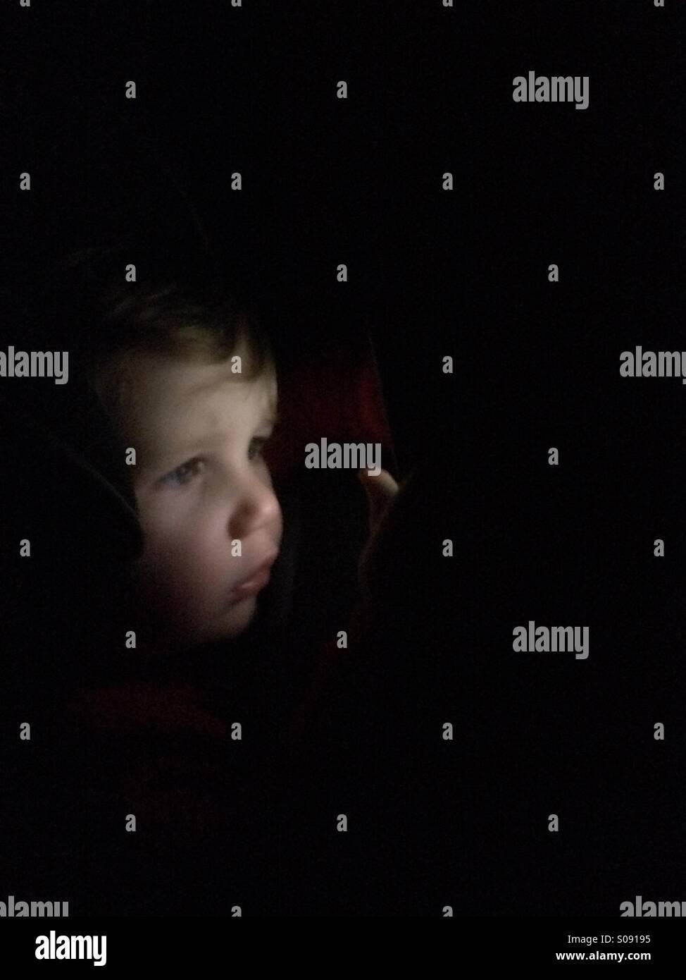 Kind auf der Suche durch die Dunkelheit Stockbild