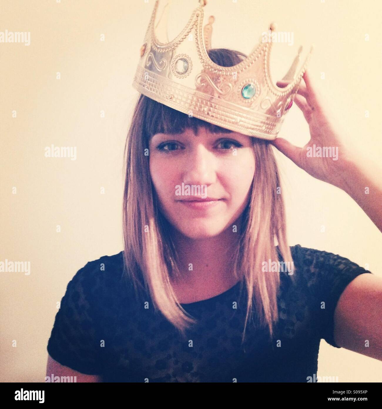 Junge Frau trägt Krone. Stockbild