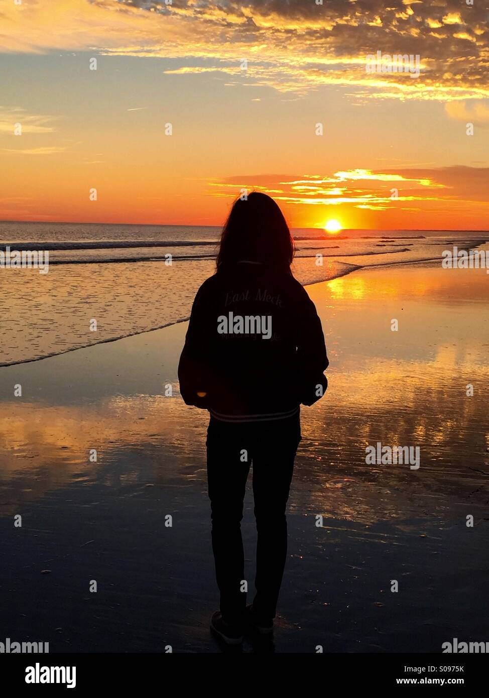 Und Frau ist Silhouette gegen den intensiven, schönen Sonnenuntergang am Strand auf Kiawah Island, South Carolina. Stockbild