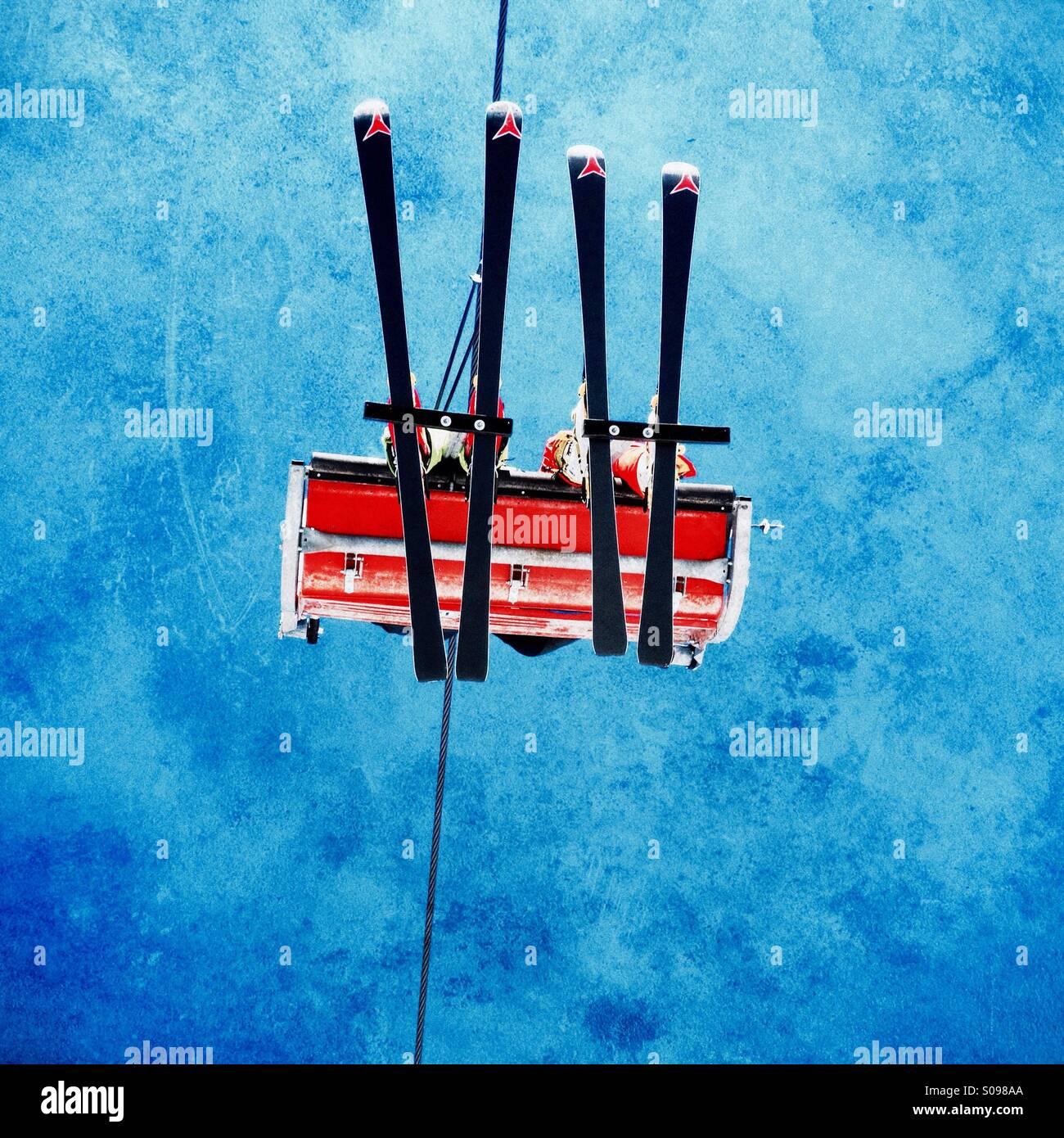 Skifahrer am Sessellift in den Alpen betrachtet von unten vor blauem Himmel Stockbild
