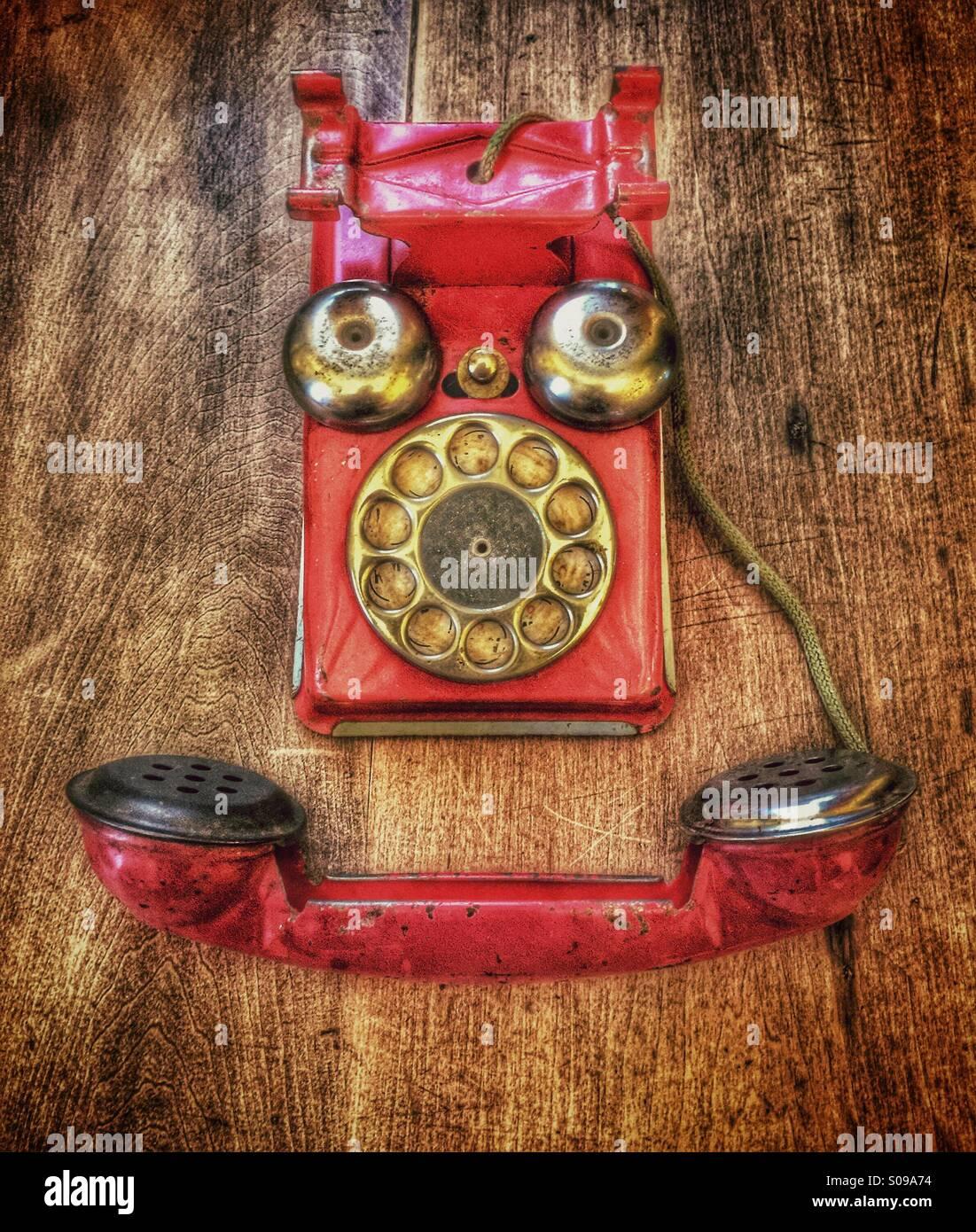 Vintage rot Spielzeug Telefon soll aussehen wie ein lächelndes Gesicht. Stockbild