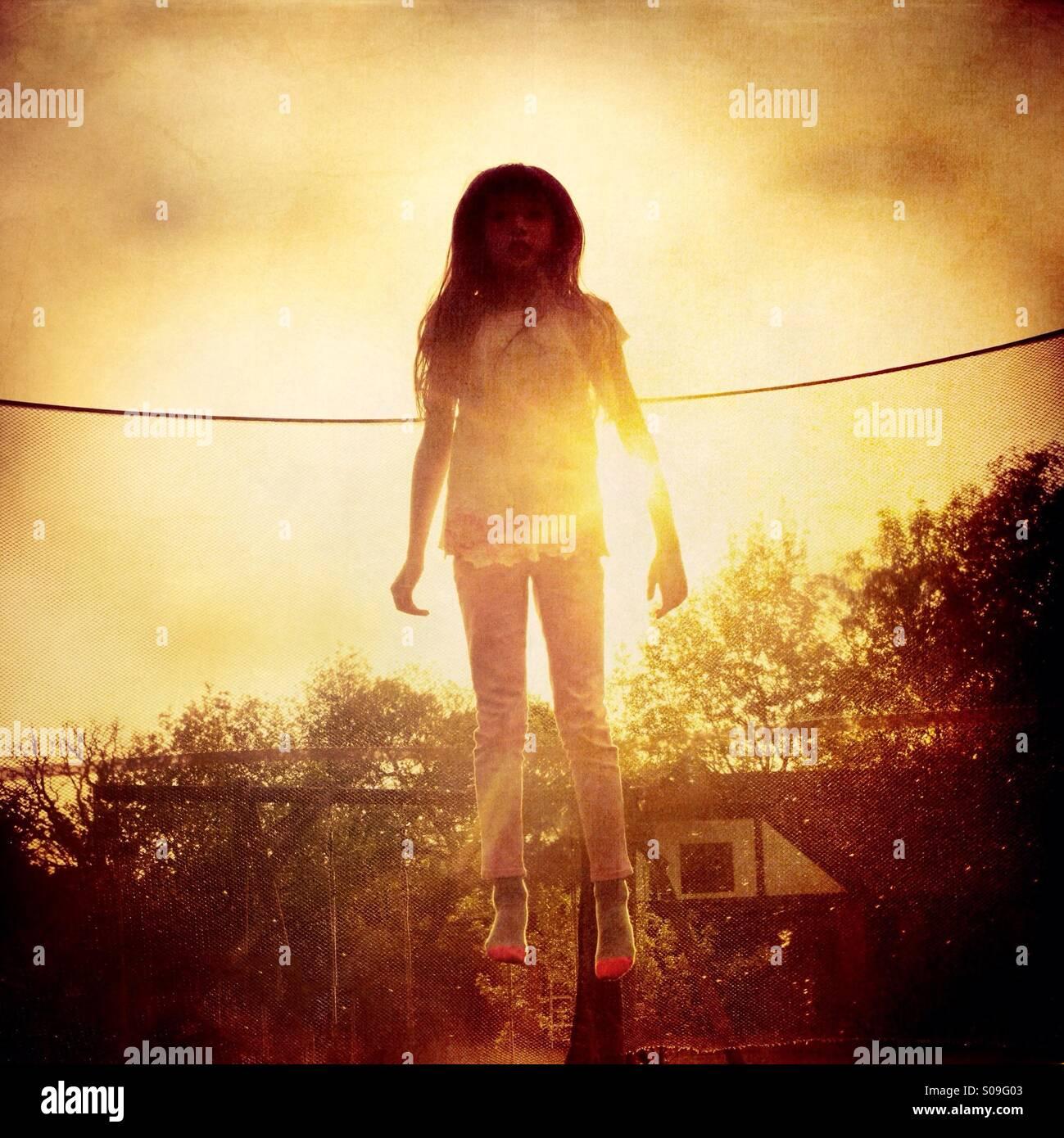 Angel - ein junges Mädchen springen auf einem Trampolin gegen die Sonne Stockbild