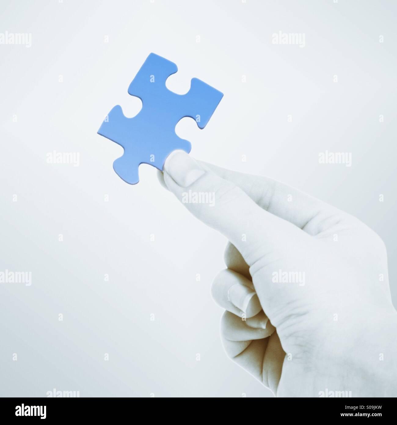 Hand, die Teil des Jigsaw Puzzles Stockbild
