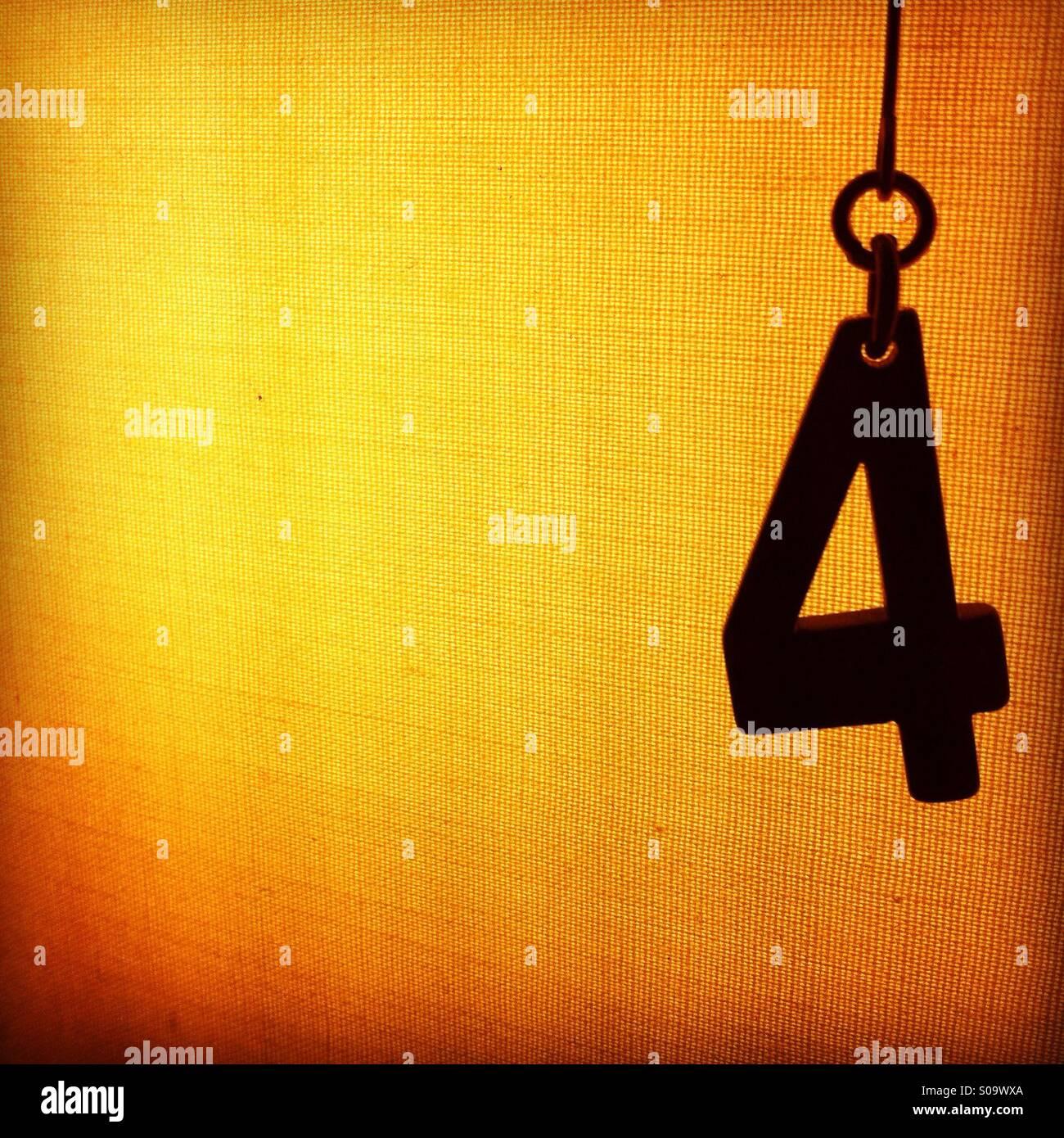 Silhouette einer Nummer vier hängenden vor einem beleuchteten strukturierten Hintergrund Stockbild