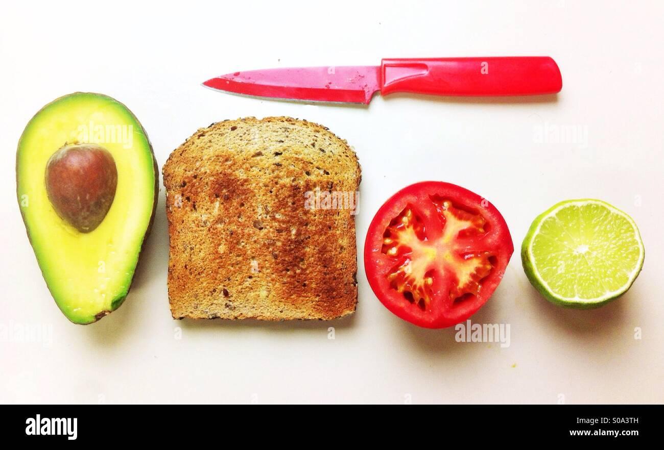 Making-of einer veganen/vegetarischen Open Sandwich mit Avocado, Tomaten und Toast Vollkornbrot. Stockbild