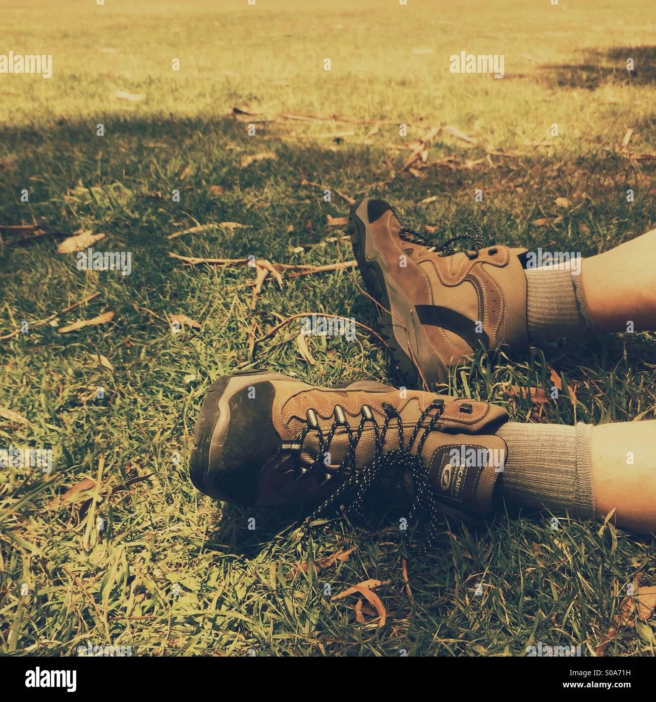Mannes Füße Wandern Stiefel sitzen auf Rasen ruht nach dem
