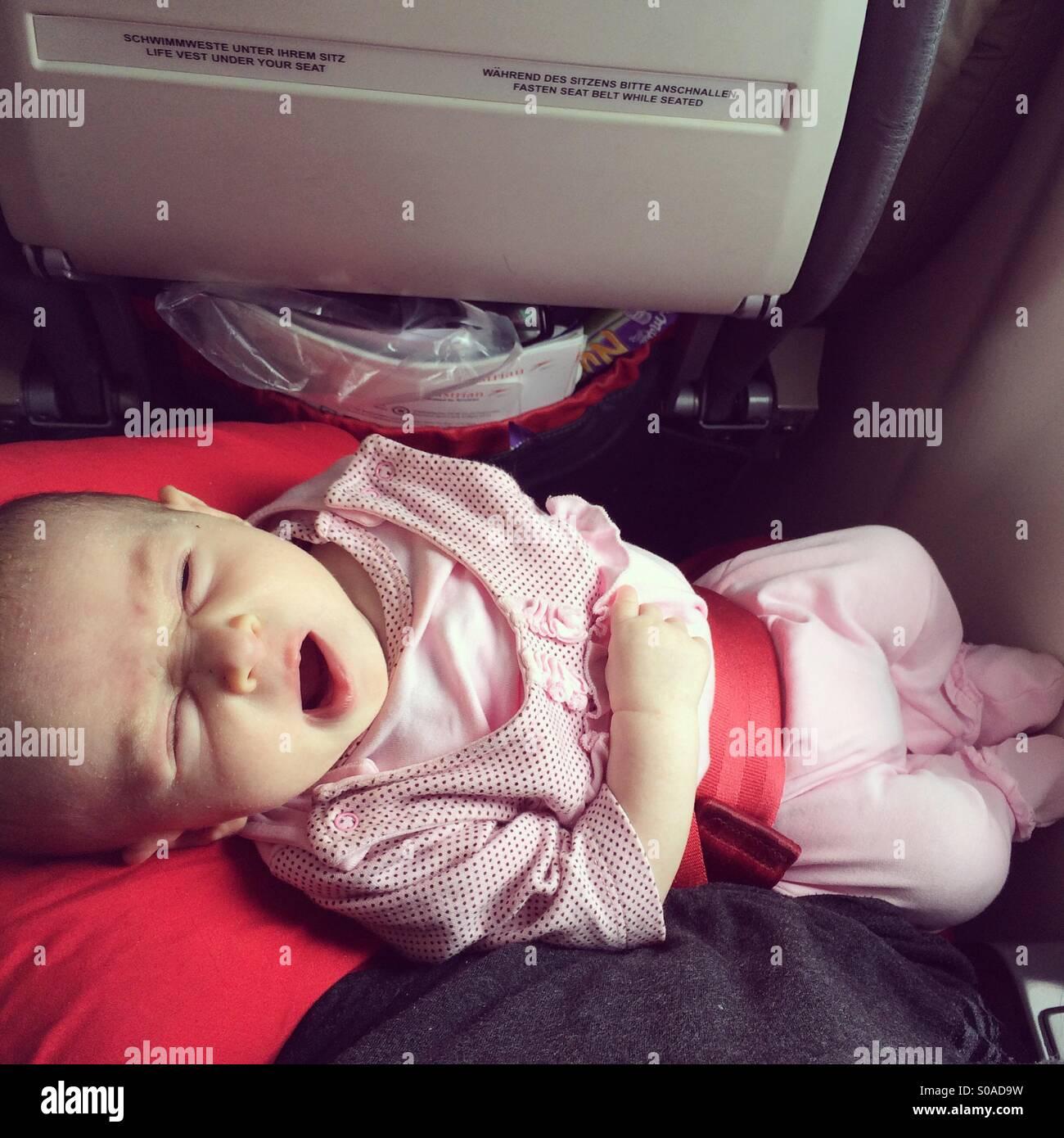 Einen Monat Baby im Flugzeug zu gähnen Stockbild