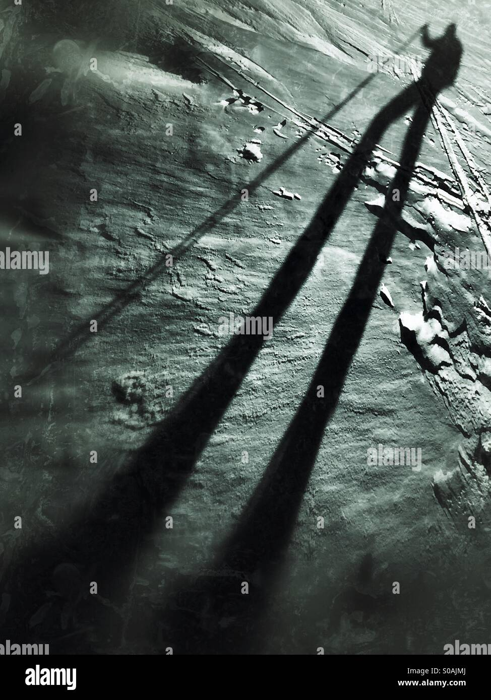 Bergsteiger wirft einen langen Schatten im Schnee. Stockbild