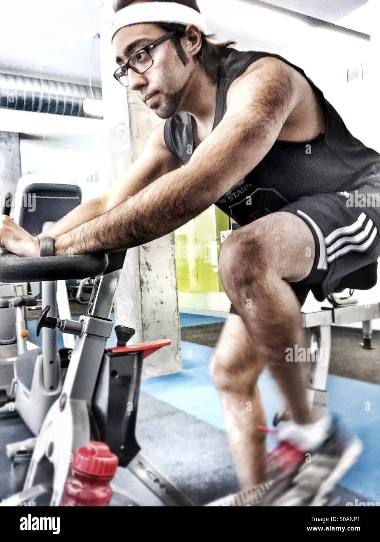 Ein Kerl in der Turnhalle auf einem stationären Fahrrad Stockbild