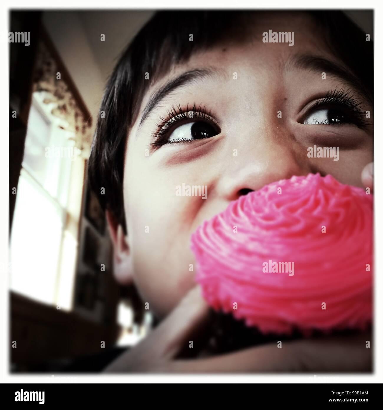 Sechs Jahre alten asiatischen kaukasischen gemischt Rennen junge nimmt einen Bissen von einem Cupcake. Stockbild