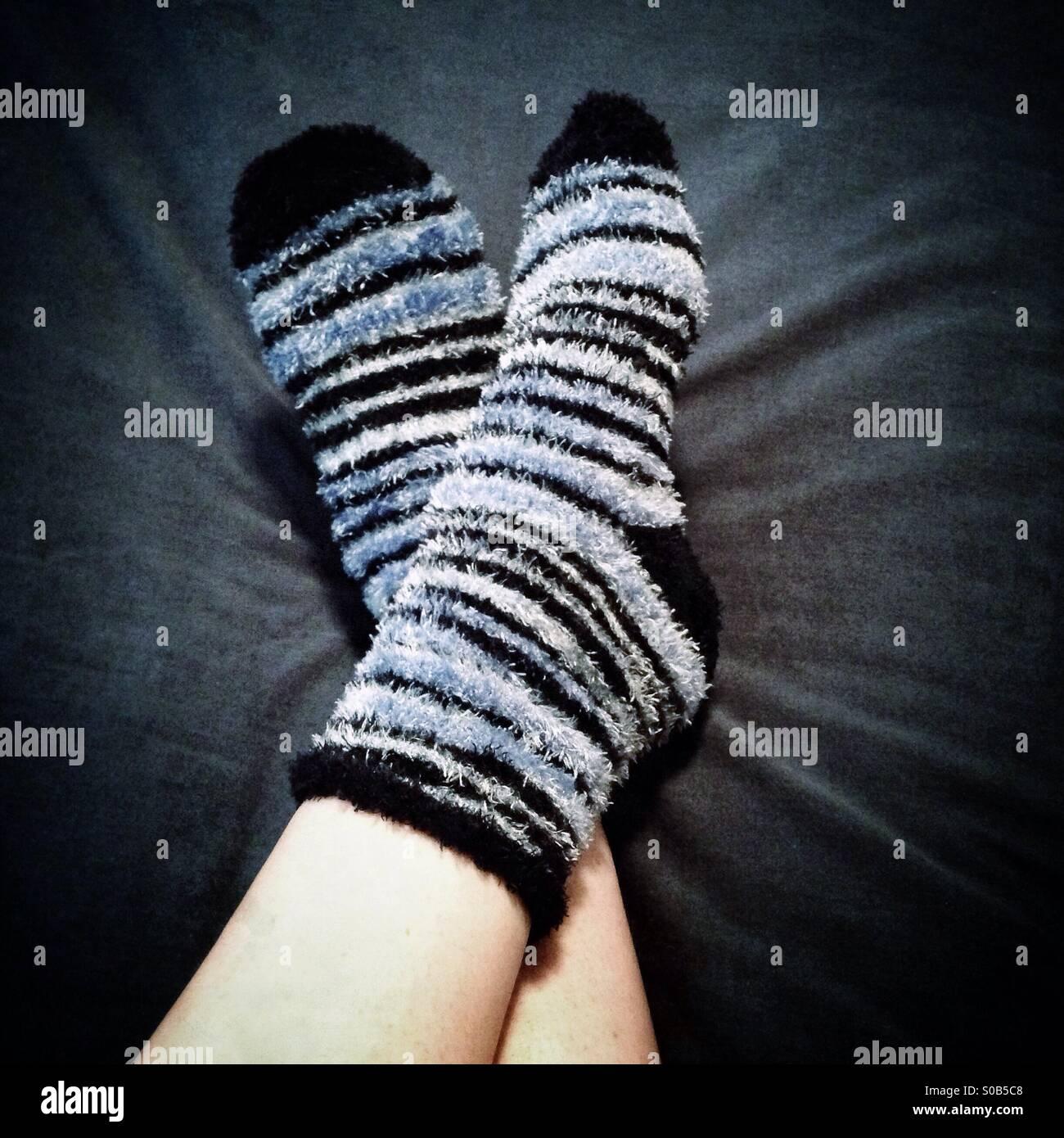 Gemütlich aussehende Füße in warme, flauschige Socken. Stockbild