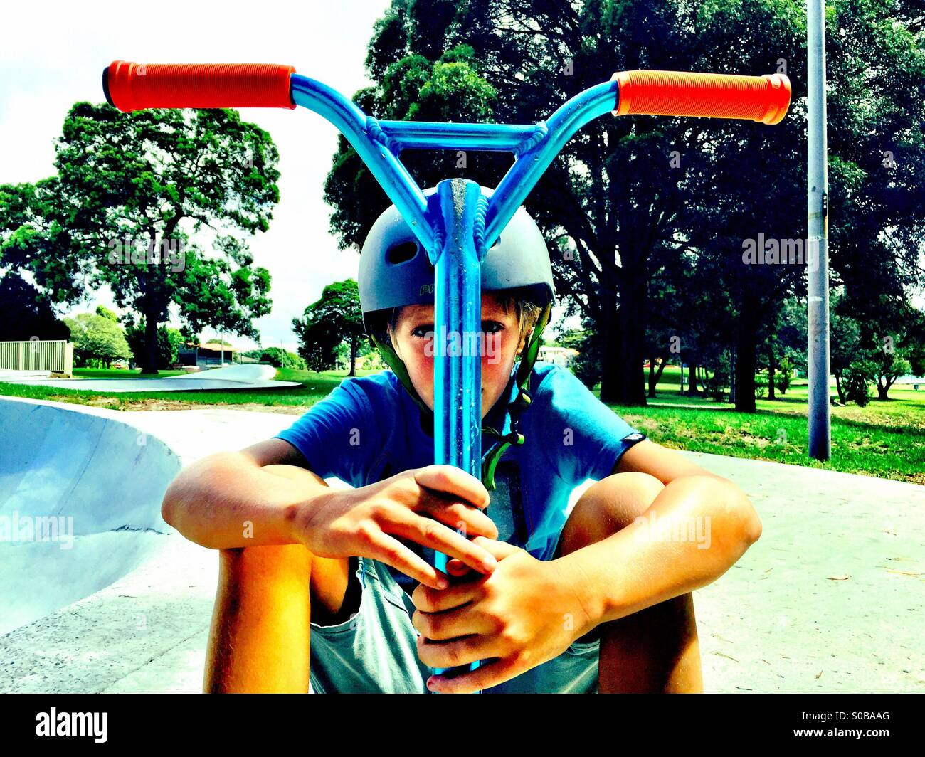 Ein zehn Jahre alter Junge mit seinem Roller Stockbild