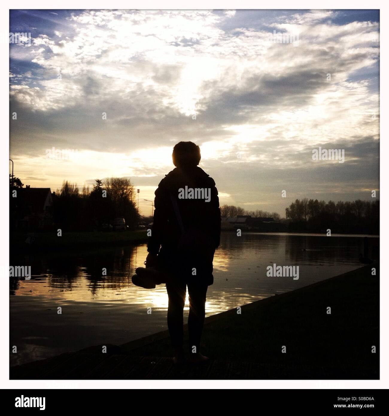 Frau stehend an einem See und Blick auf den Sonnenuntergang Stockbild