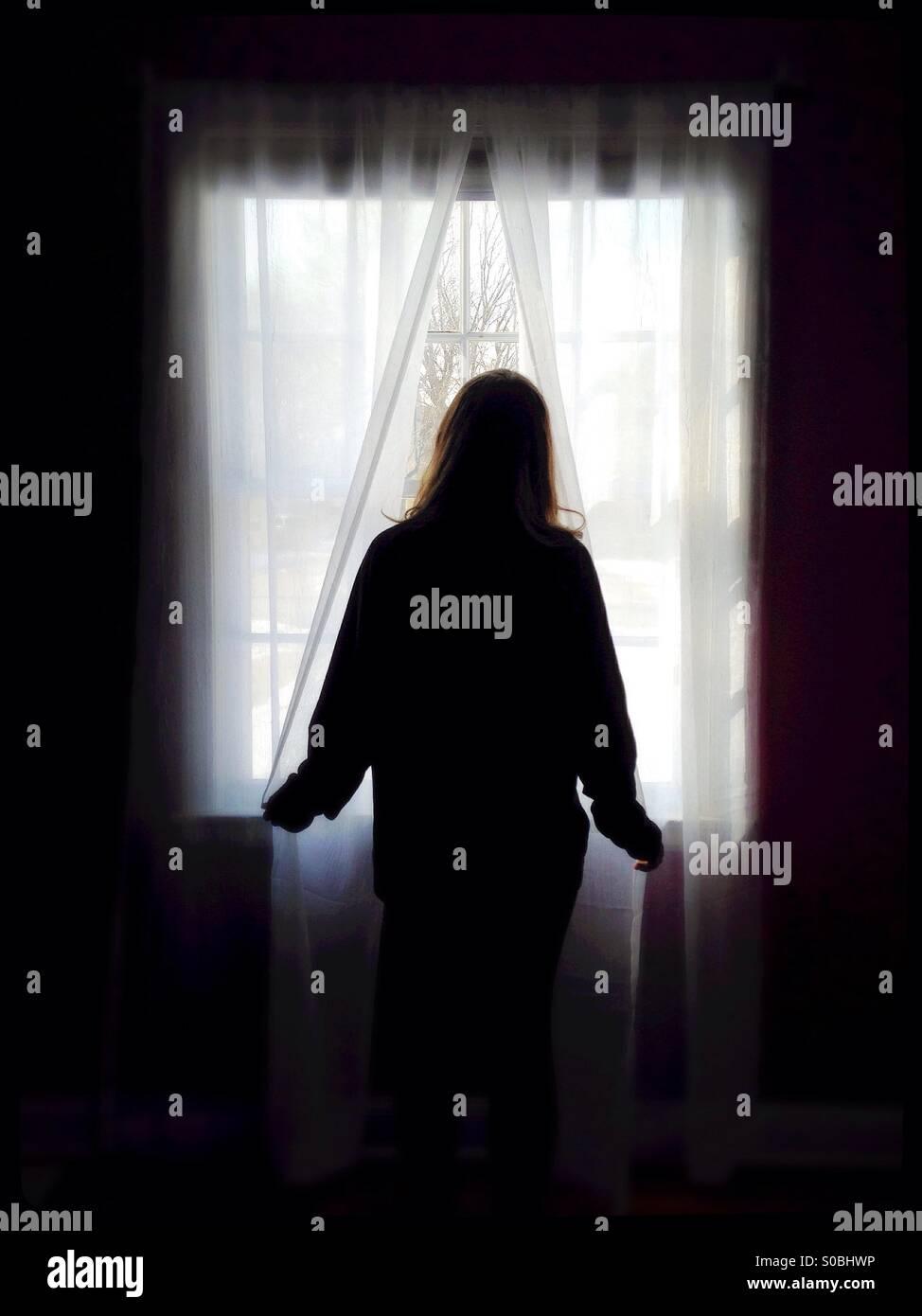 Eine Frau steht am Fenster, auf der Suche. Stockbild