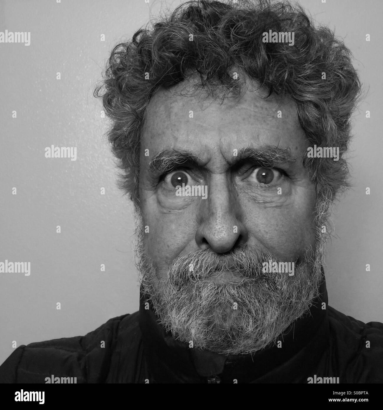 Weißer Mann, Alter 64, mit Bart und Ausdruck von Wut und Frustration, close-up, Seattle, USA Stockbild
