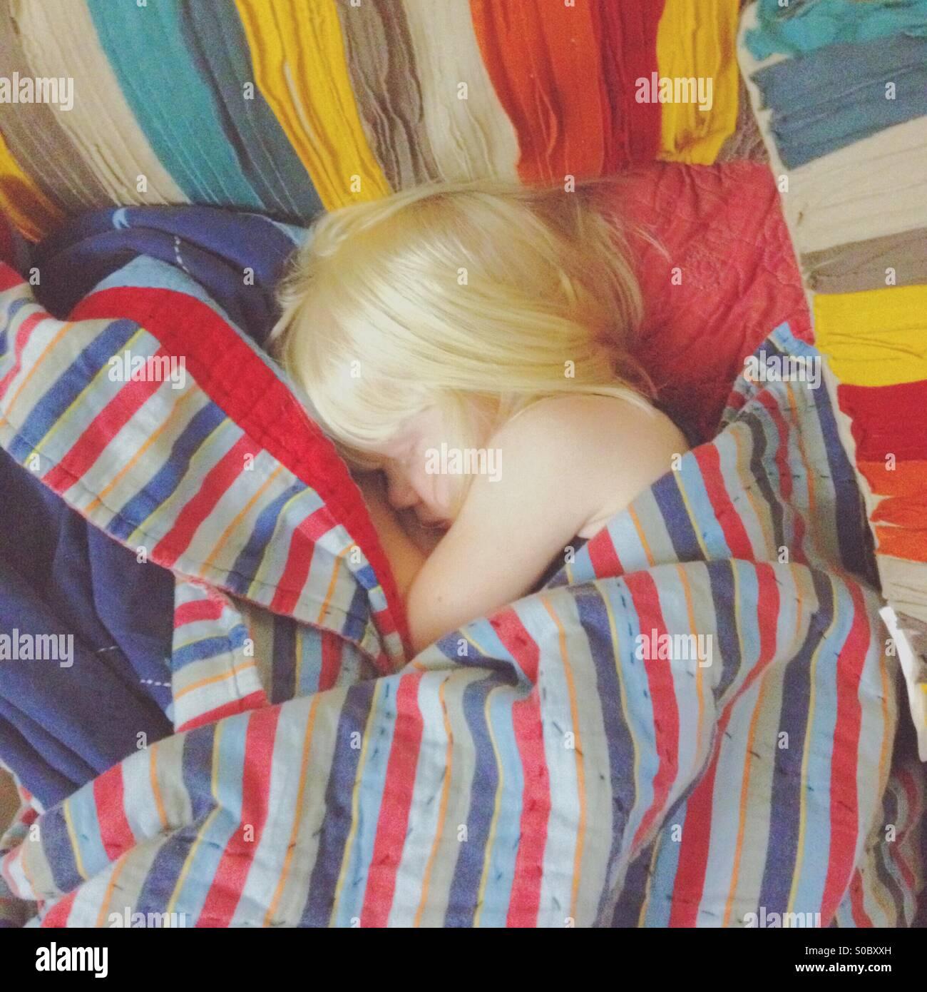 Junge blondes Mädchen schlief eingewickelt in einer Reihe von bunten decken. Stockbild