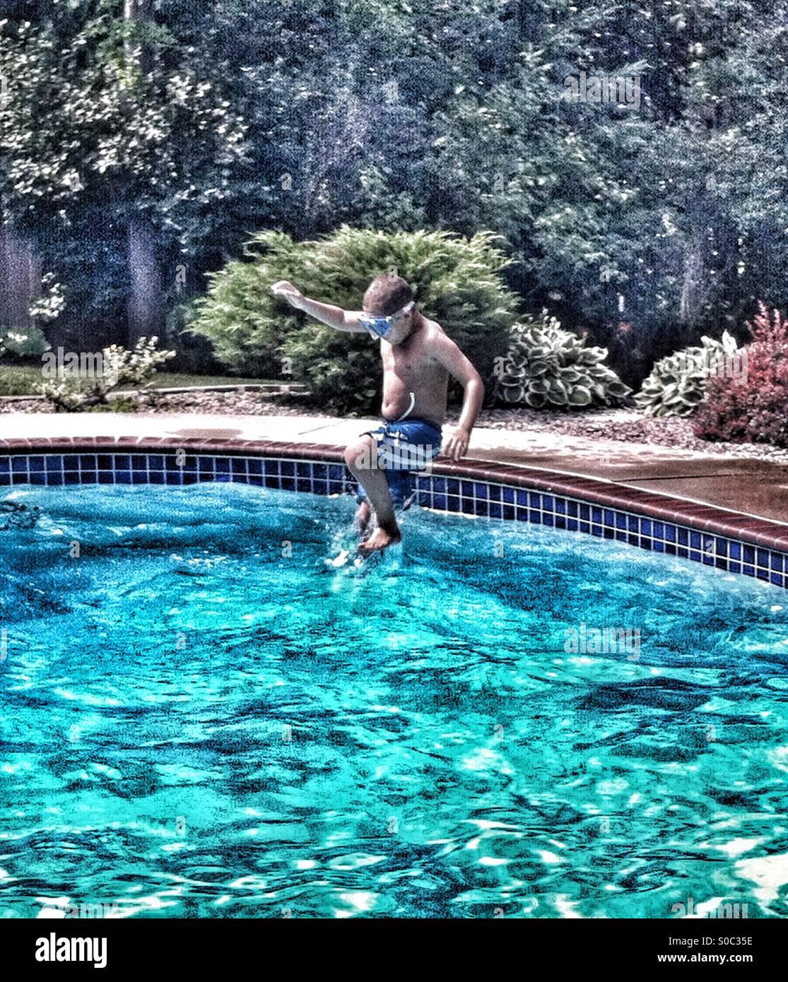 Junge nimmt Kanonenkugel Sprung ins Schwimmbad Stockbild