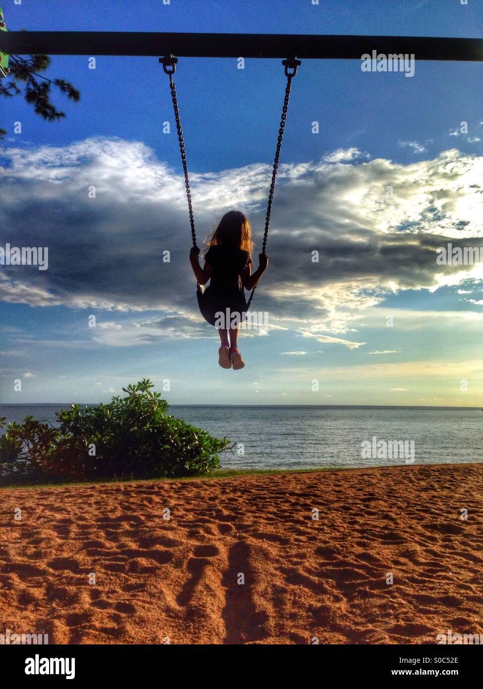 Junges Mädchen auf einer Schaukel am Strand. Stockfoto