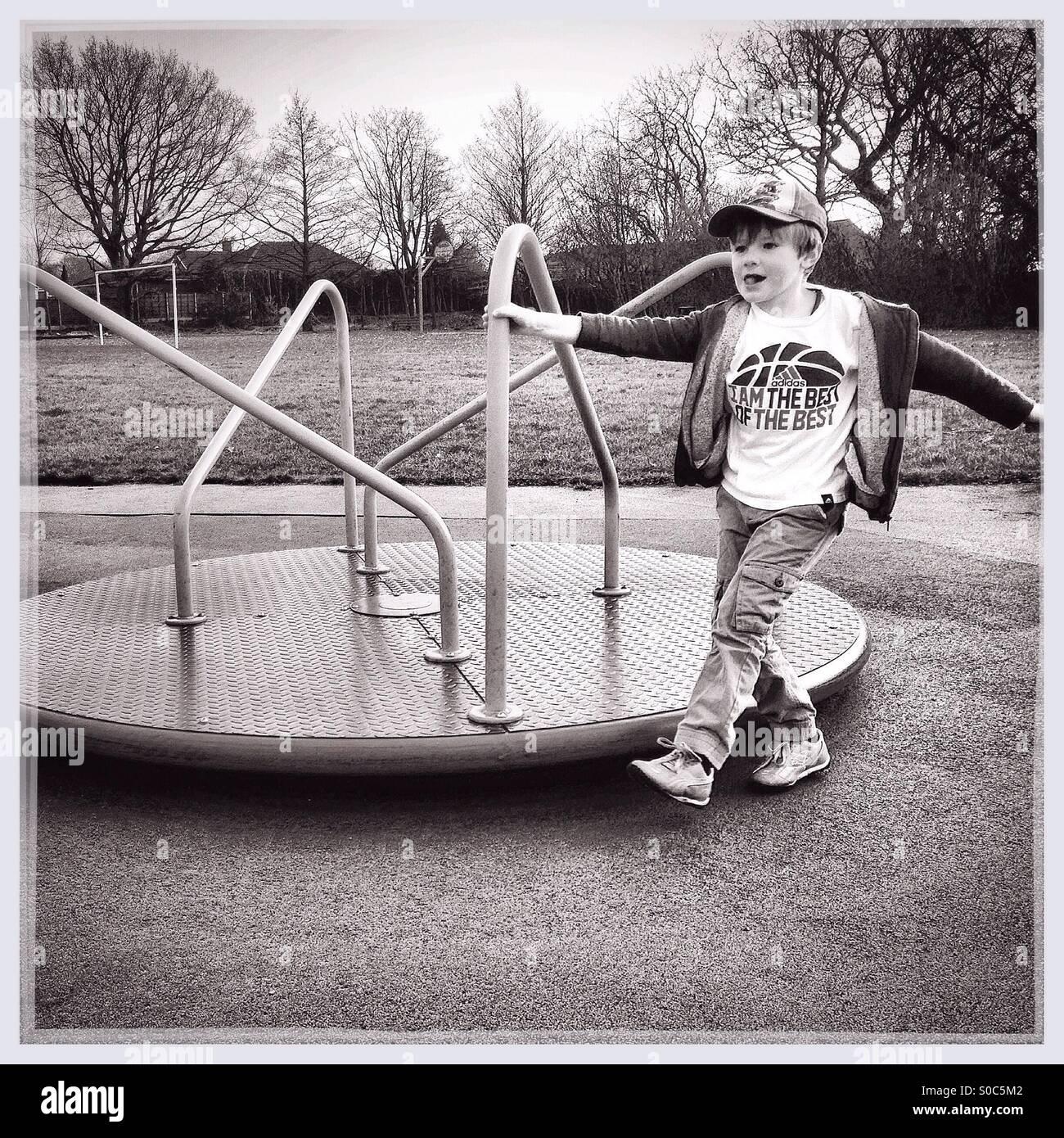 Junge spielt auf einem Kreisverkehr Stockbild
