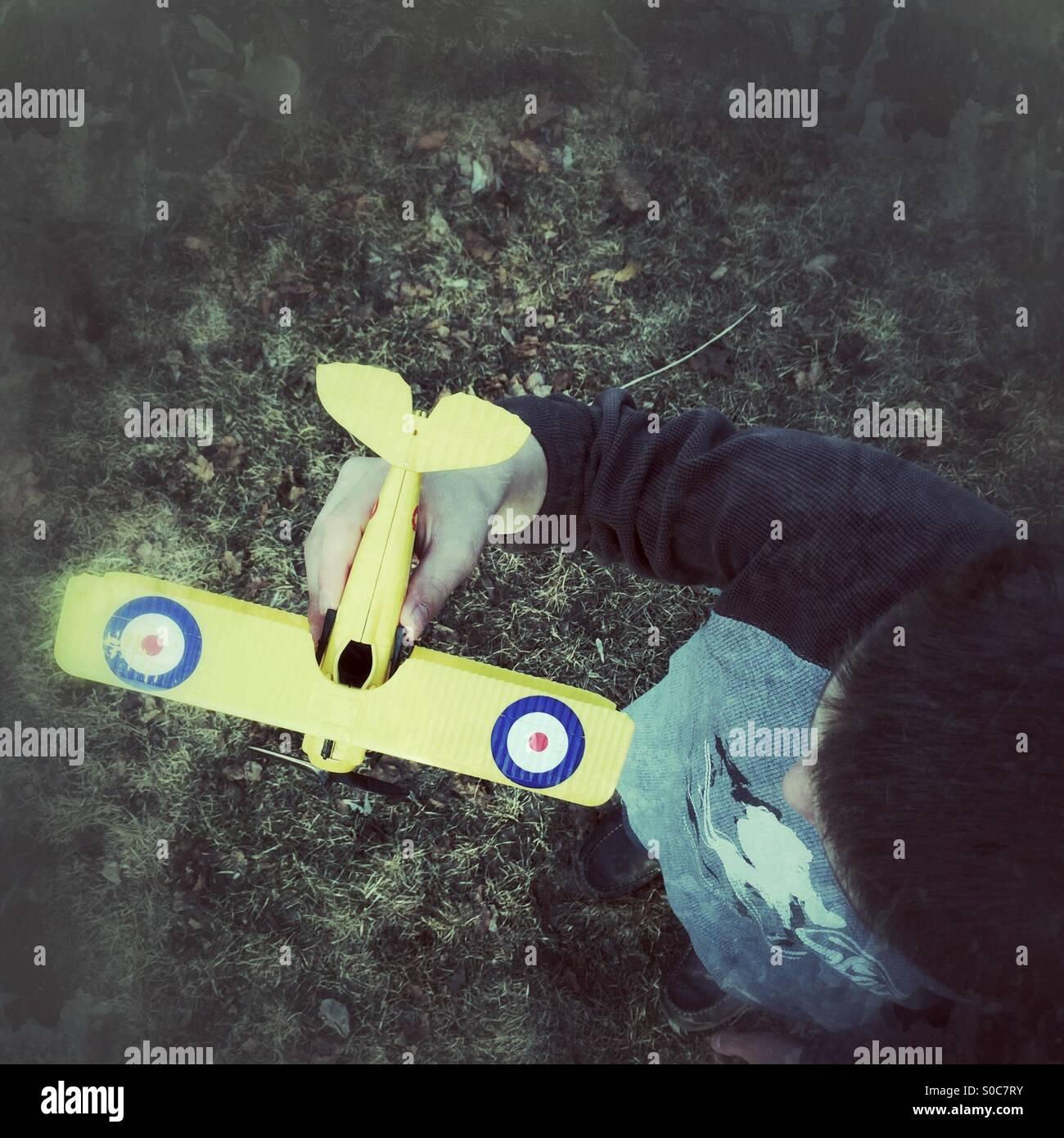 Blickte auf ein Junge hält ein Modellflugzeug Stockbild