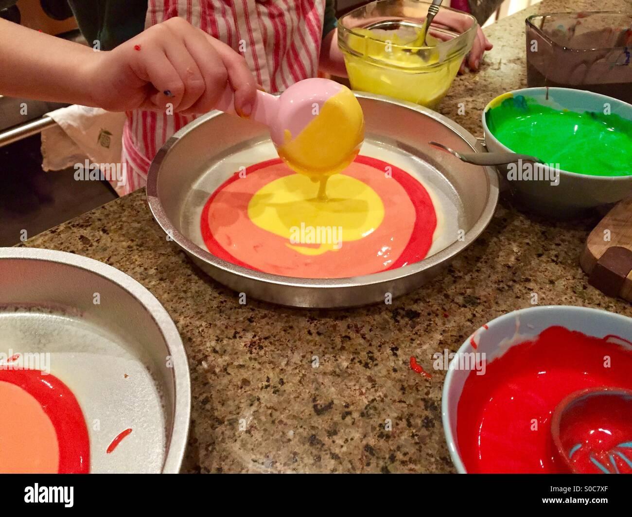 Ein Kind gießt bunten gelben Kuchenteig in eine Kuchenform auf einen unordentlichen Küchentisch. Stockbild
